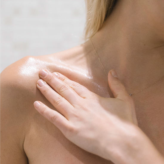 Applying body oil to the shoulders