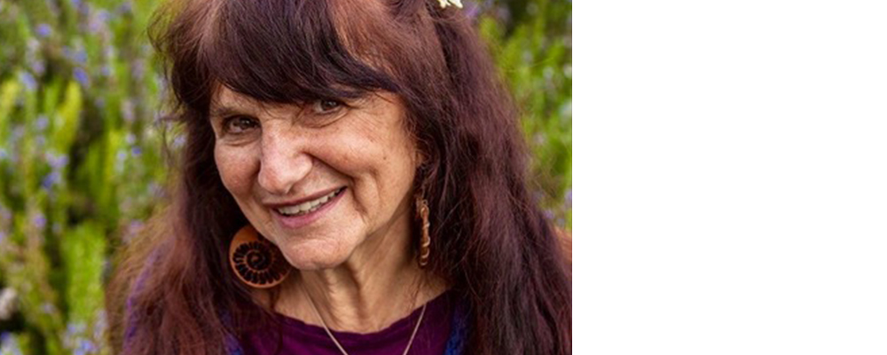 Herbalist Rosemary Gladstar smiling and hold herbs