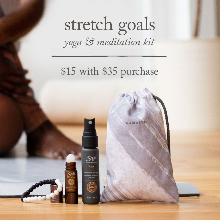Stretch Goals Yoga and Meditation Kit displayed in foreground with woman sitting on a yoga mat in the background stretching