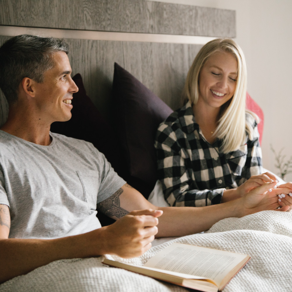 Couple in bed supporting each other