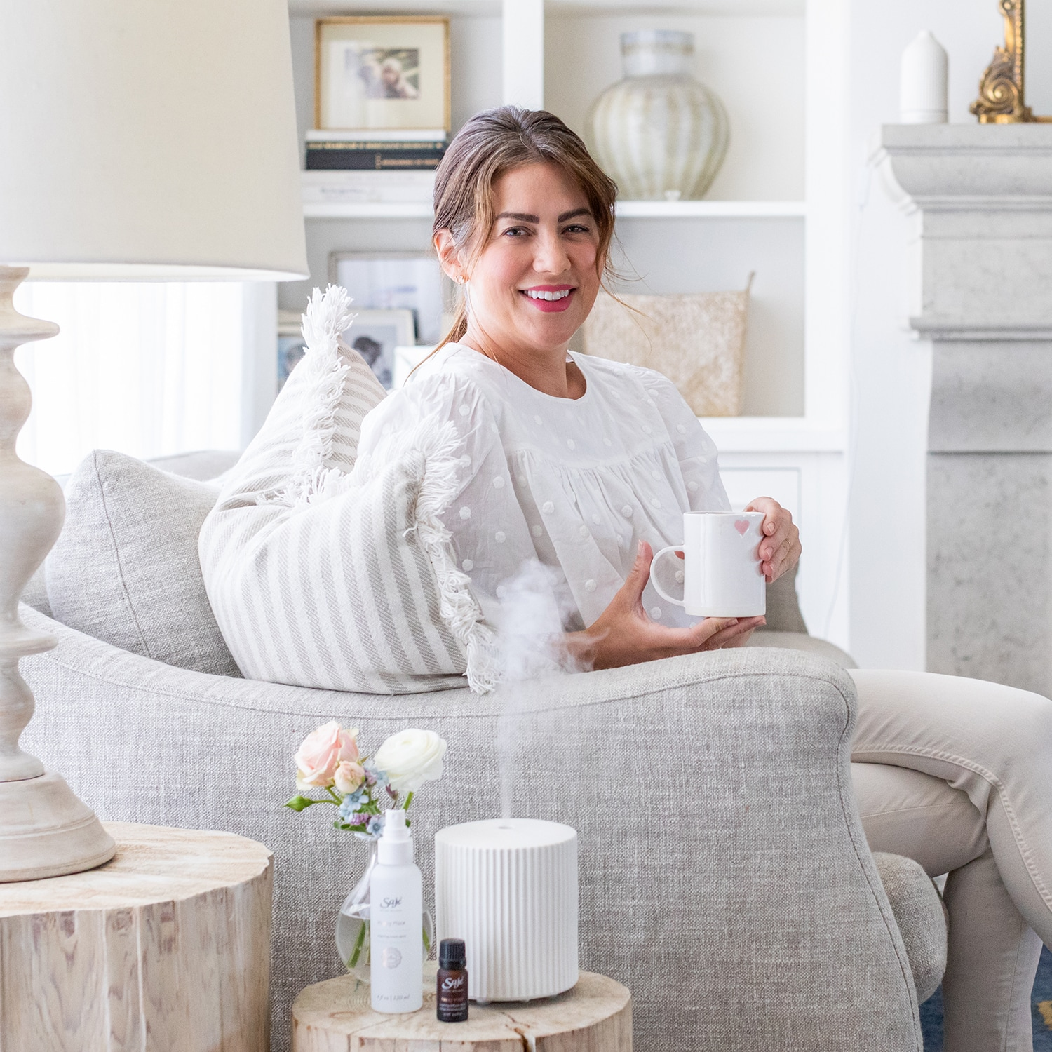 Jillian Harris sitting on chair with mug, in front of Saje x Jillian Harris collaboration diffuser, diffuser blend and room spray