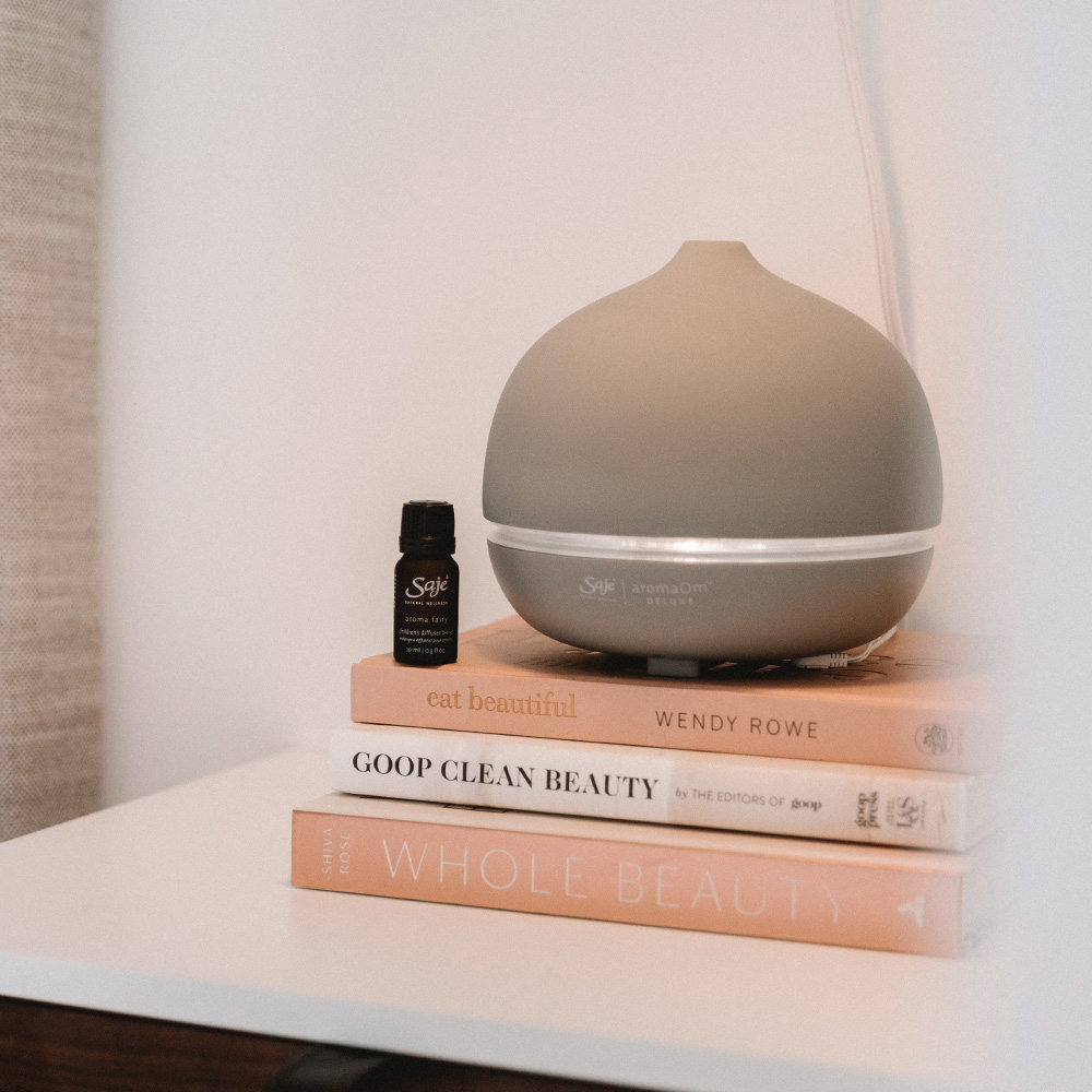 Saje diffuser and essential oil beside bed