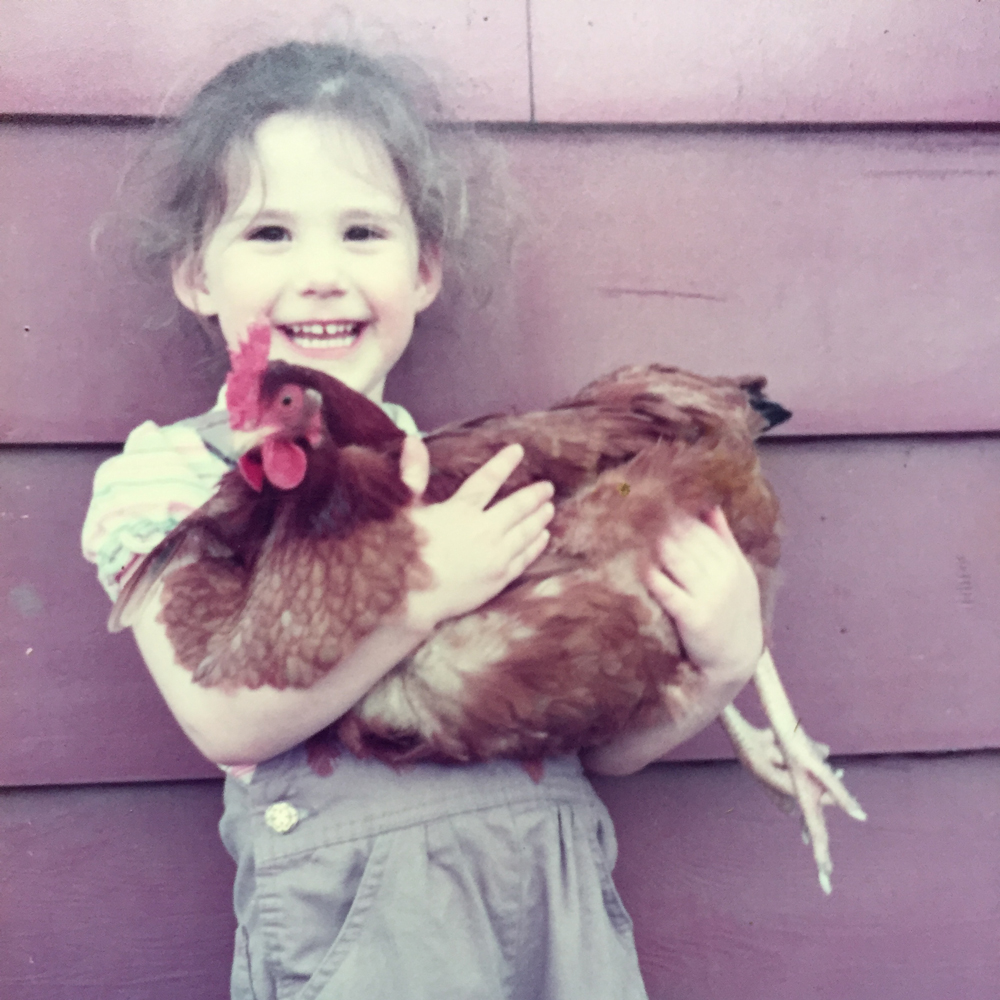 Girl carrying a chicken
