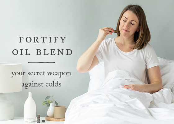 woman in bed rolling Fortify Essential Oil Roll-On, her secret weapon against colds