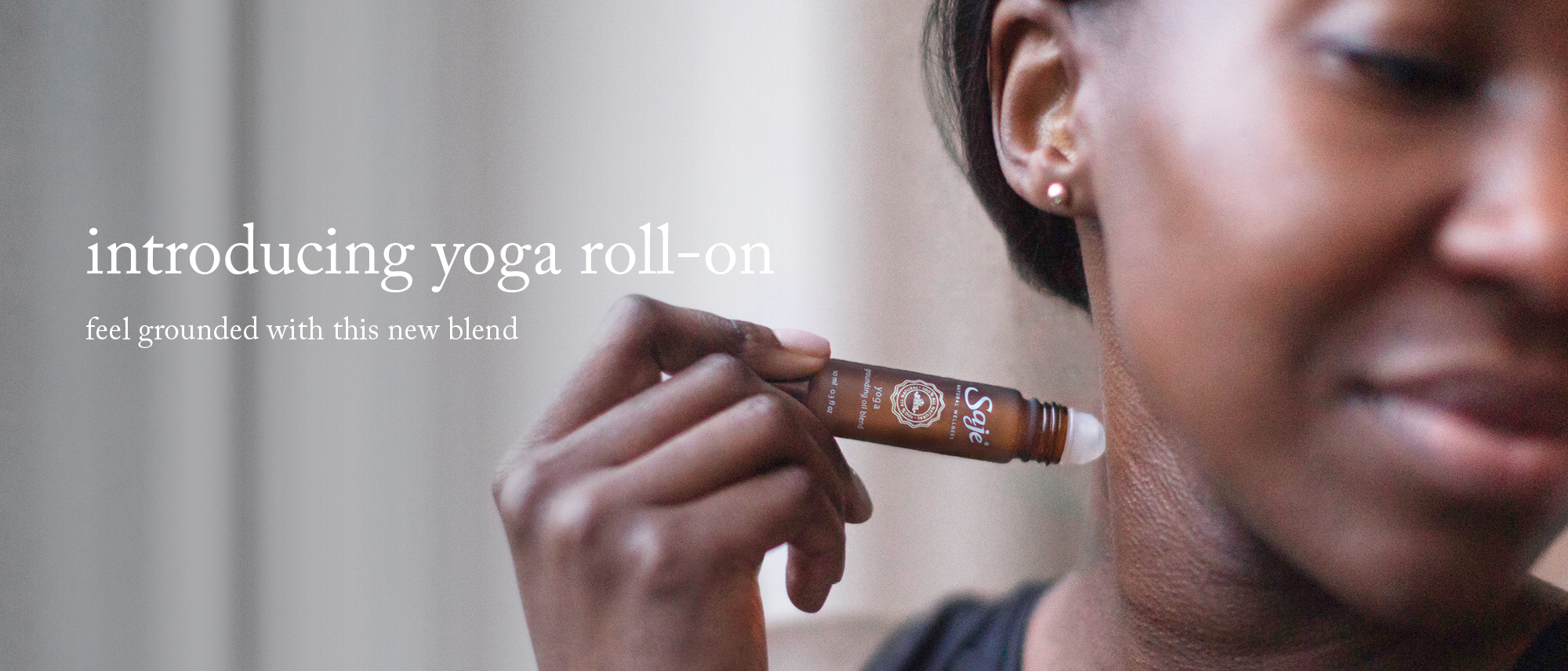 Woman rolling Yoga Oil Blend on neck