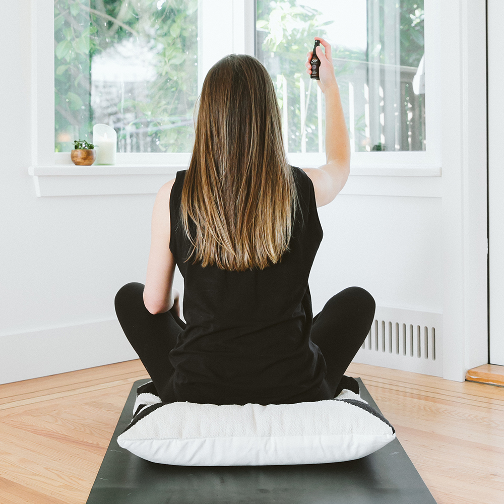 Woman meditating in front of a window.