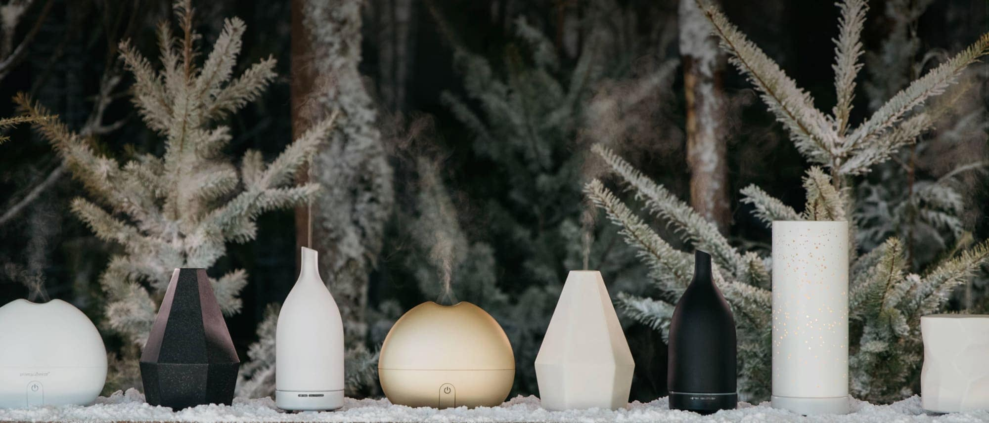 saje diffusers displayed beside each other against forest background