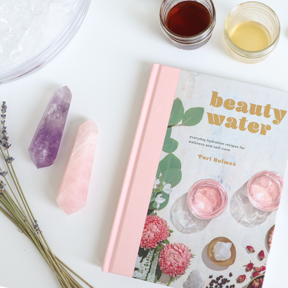 Beauty Water book by Tori Holmes beside crystals