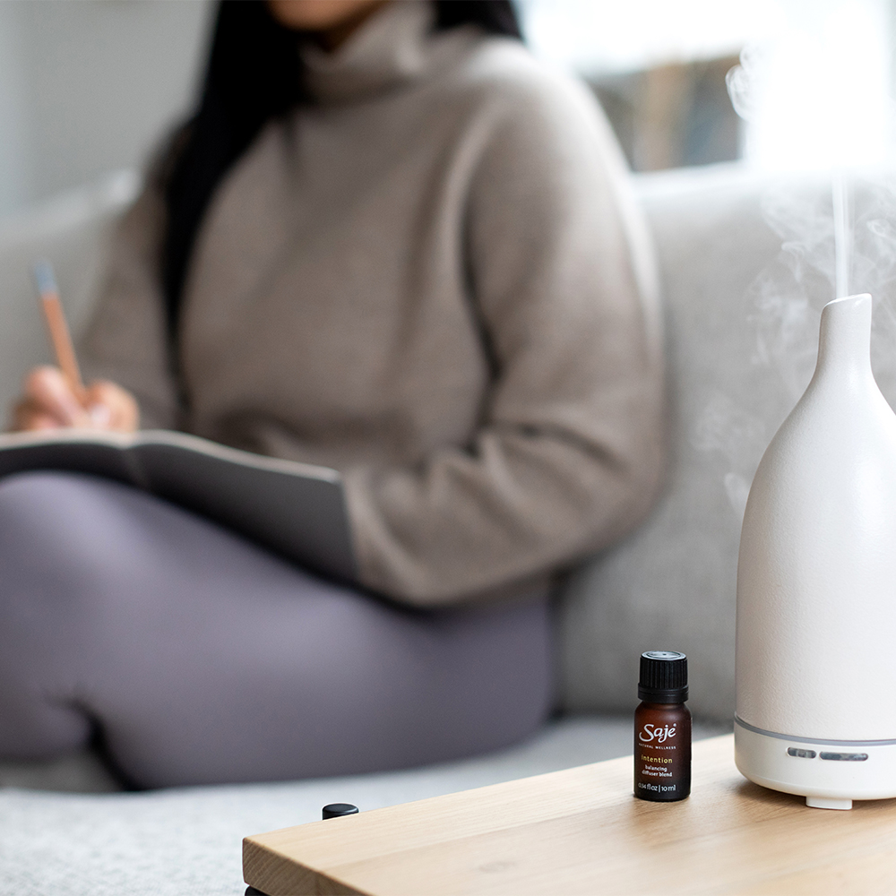 Person journalling with Aroma Om Diffuser