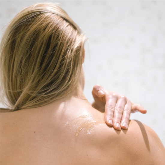 Massaging body oil onto the back